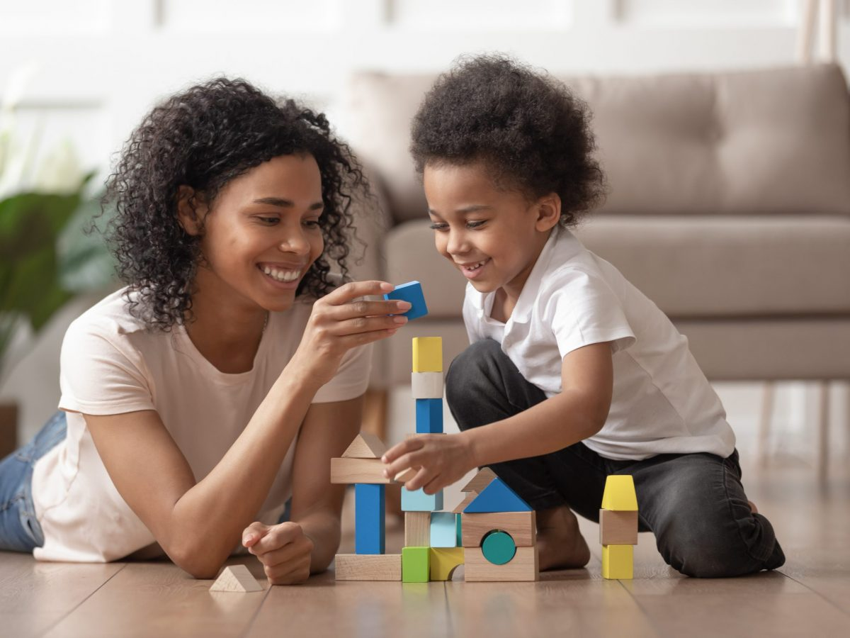 Smiling african mother baby sitter play with little kid son lay on warm floor, caring black mother nanny help teach child boy build constructor of wooden blocks at home, daycare, children development